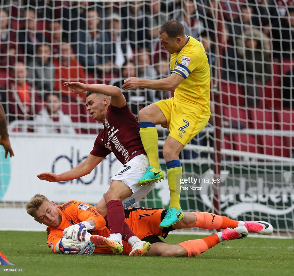George Long of AFC Wimbledon saves at the feet of Billy Waters of Northampton Town and team mate Barry Fuller during the Sky Bet League One match between Northampton Town and A.F.C. Wimbledon at Sixfields on October 14, 2017 in Northampton, England.