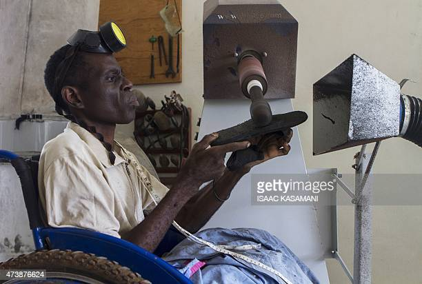 George Lwingirya an artisan works on an orthopaedic shoe at the Comprehensive Rehabilitation Services Uganda in Wakiso on April 24 2015 AFP PHOTO/...