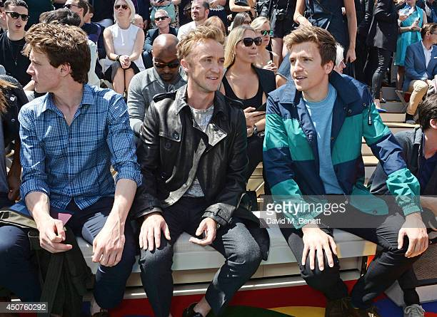 George MacKay Tom Felton and Greg James attend the front row at Burberry Prorsum SS15 during London Collections Men at Kensington Gardens on June 17...