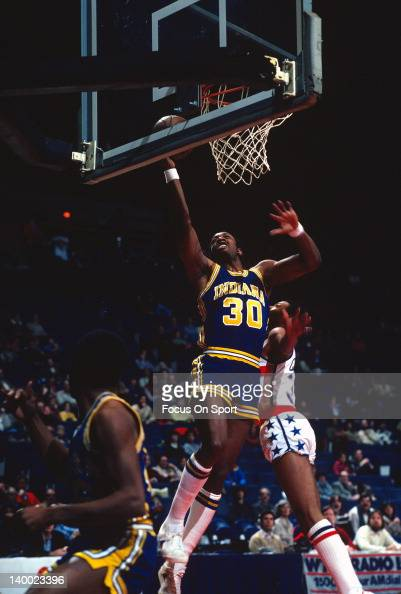George McGinnis of the Indiana Pacers lays the ball up over Austin Carr of the Washington Bullets during an NBA basketball game circa 1980 at the...