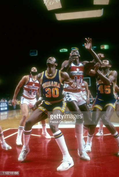 George McGinnis of the Indiana Pacers looks to get position on Elvin Hayes of the Washington Bullets during an NBA basketball game circa 1980 at the...