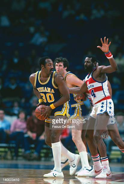 George McGinnis of the Indiana Pacers looks to pass the ball guarded by Spencer Haywood of the Washington Bullets during an NBA basketball game circa...