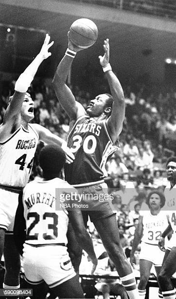 George McGinnis of the Philadelphia 76ers drives to the basket while guarded Kevin Kunnert of the Houston Rockets at The Summit in Houston Texas...