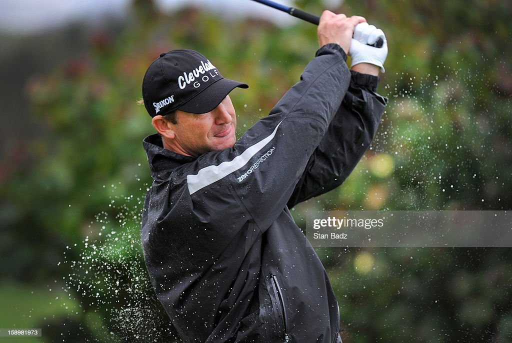 George McNeill hits a drive on the first hole as rain droplets splash from his body during the first round of the Hyundai Tournament of Champions at Plantation Course at Kapalua on January 4, 2013 in Kapalua, Hawaii.