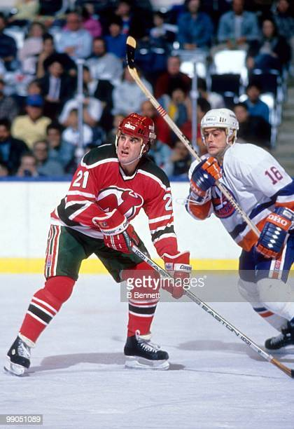 George McPhee of the New Jersey Devils defends against Pat LaFontaine of the New York Islanders during an NHL game circa 1987 at the Nassau Coliseum...