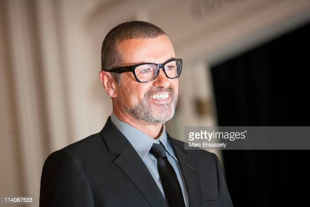 George Michael poses for photos before announcing his 'Symphonica' European Orchestral tour during a press conference at the Royal Opera House on May...