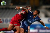 George Moala of the Blues offloads in the tackle of James Hanson of the Reds during the round 12 Super Rugby match between the Blues and the Reds at...