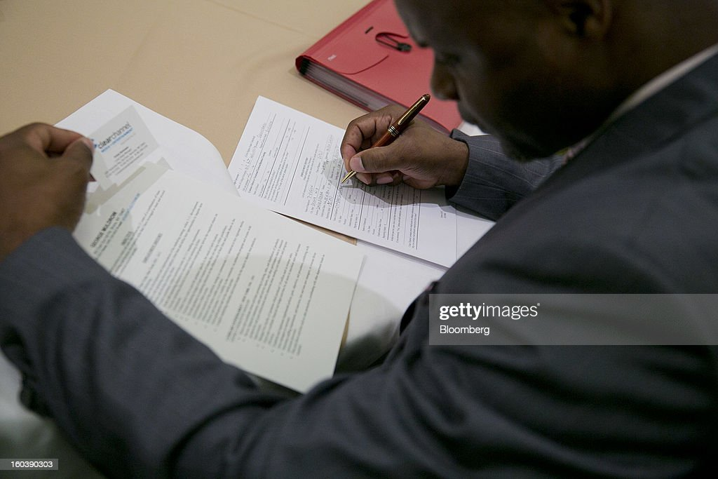George Muldrow fills out a job application at a National Career Fairs job fair in Arlington, Virginia, U.S., on Wednesday, Jan. 30, 2013. The U.S. Labor Department is scheduled to release initial jobless claims data on Jan. 31. Photographer: Andrew Harrer/Bloomberg via Getty Images