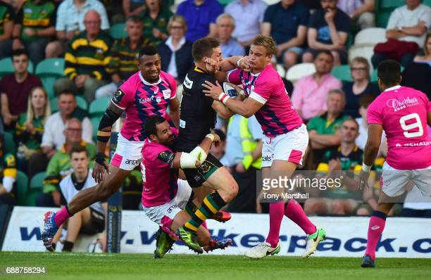 George North of Northampton Saints is tackled by Geoffrey Doumayrou and Jules Plisson of Stade Francais during the Champions Cup Playoff Final...