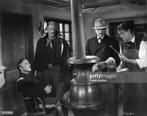 George O'Brien Harry Woods and John Wayne look on as Arthur Shields playing Dr O'Laughlin inspects a bullet in a scene from the RKO western 'She Wore...