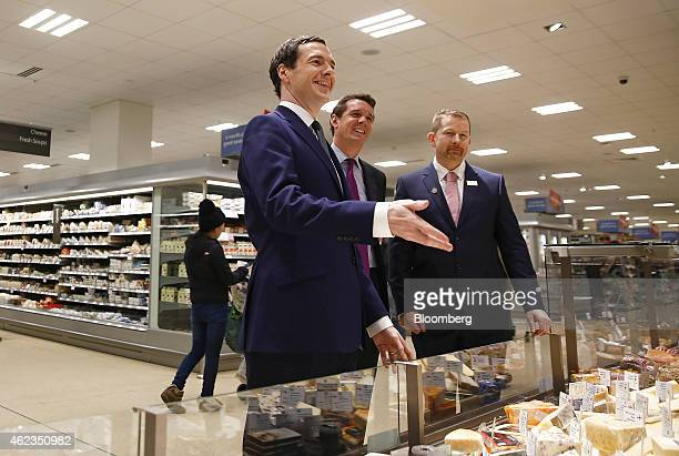 George Osborne UK chancellor of the exchequer center gestures whilst speaking to staff at the cheese and delicatessen counter during a visit to a...
