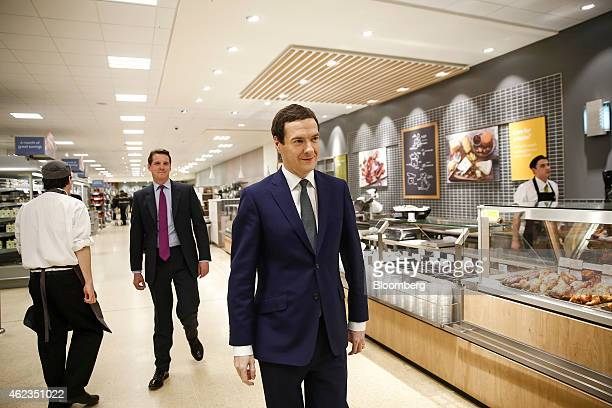 George Osborne UK chancellor of the exchequer center passes the cheese and delicatessen counter during a visit to a Waitrose Ltd supermarket in the...