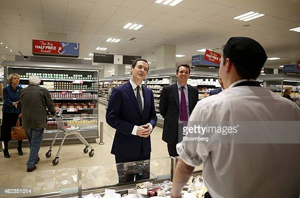 George Osborne UK chancellor of the exchequer center speaks to staff at the cheese and delicatessen counter during a visit to a Waitrose Ltd...
