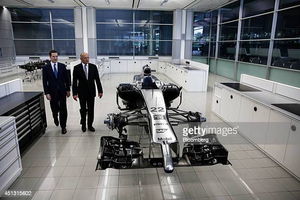 George Osborne UK chancellor of the exchequer left and Ron Dennis chairman of McLaren Automotive Ltd walk past Jenson Button's McLaren Formula One...