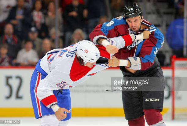 George Parros of the Montreal Canadiens and Patrick Bordeleau of the Colorado Avalanche engage in a fight in the first period at Pepsi Center on...