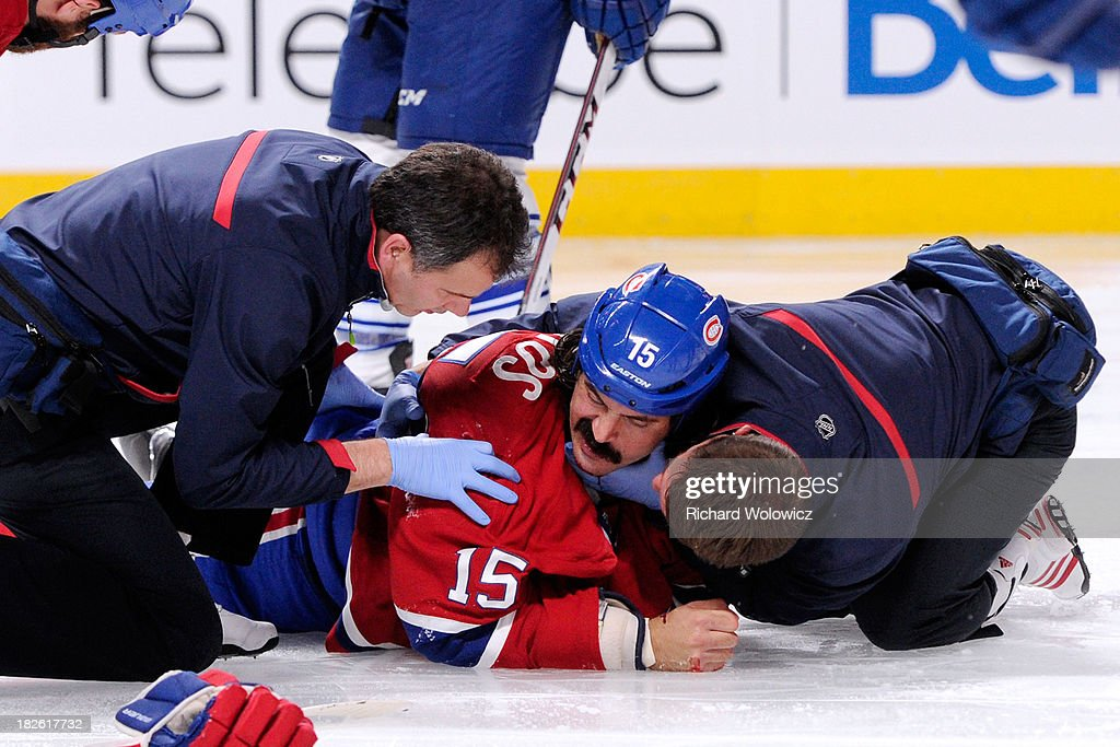 <a gi-track='captionPersonalityLinkClicked' href=/galleries/search?phrase=George+Parros&family=editorial&specificpeople=557239 ng-click='$event.stopPropagation()'>George Parros</a> #15 of the Montreal Canadiens is tended to by Canadiens staff after falling head first on the ice during a fight in the NHL game against the Toronto Maple Leafs at the Bell Centre on October 1, 2013 in Montreal, Quebec, Canada. The Maple Leafs defeated the Canadiens 4-3.