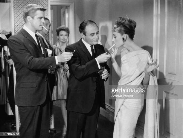 George Peppard and Martin Balsam offer to light Audrey Hepburn's cigarette in a scene from the film 'Breakfast At Tiffany's' 1961