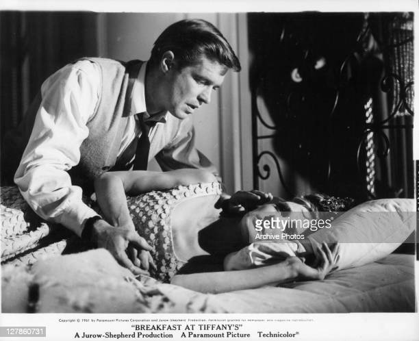 George Peppard leaning over Audrey Hepburn in bed in a scene from the film 'Breakfast At Tiffany's' 1961