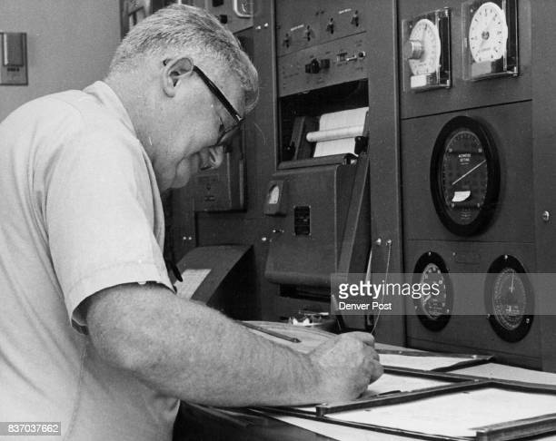 George Porter logs data from instruments on board Large dial in center is altimeter which shows barometric pressure important to pilots making...