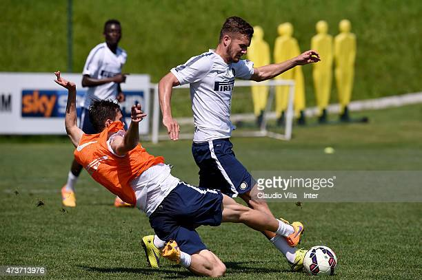 George Puscas and Marco Andreolli compete for the ball during FC Internazionale training session at the club's training ground at Appiano Gentile on...