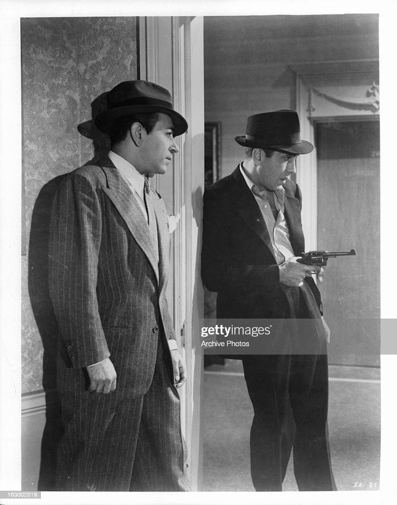George Raft watches as <a gi-track='captionPersonalityLinkClicked' href=/galleries/search?phrase=Humphrey+Bogart&family=editorial&specificpeople=70004 ng-click='$event.stopPropagation()'>Humphrey Bogart</a> points a gun in a scene from the film 'Invisible Stripes', 1939.