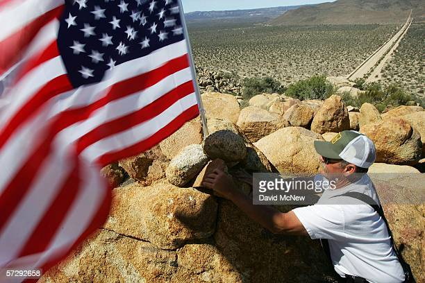 George Royse of Long Beach California raises a US flag at his post overlooking the border fence that divides Mexico from the US as the Minuteman...