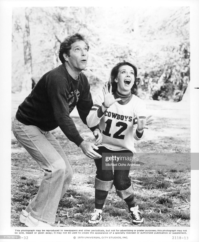George Segal and Natalie Wood play football in a scene from the film 'The Last Married Couple in America', 1980.