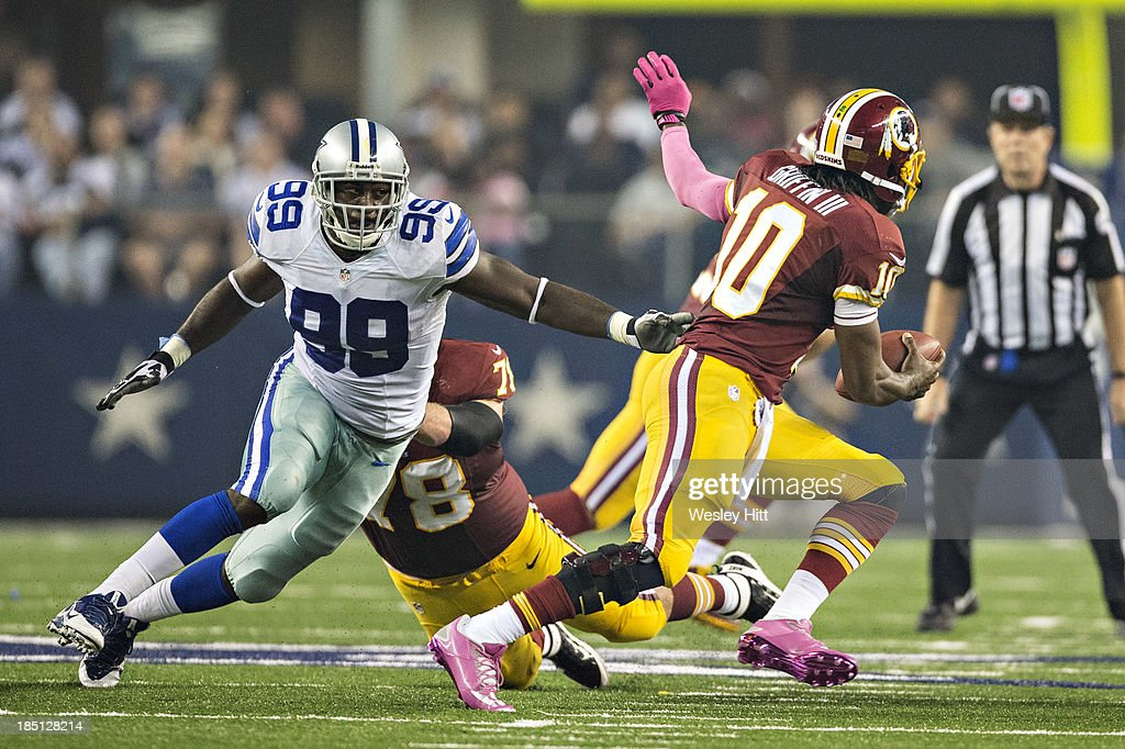 <a gi-track='captionPersonalityLinkClicked' href=/galleries/search?phrase=George+Selvie&family=editorial&specificpeople=4483733 ng-click='$event.stopPropagation()'>George Selvie</a> #99 of the Dallas Cowboys chases after <a gi-track='captionPersonalityLinkClicked' href=/galleries/search?phrase=Robert+Griffin&family=editorial&specificpeople=2495030 ng-click='$event.stopPropagation()'>Robert Griffin</a> III #10 of the Washington Redskins at AT&T Stadium on October 13, 2013 in Arlington, Texas. The Cowboys defeated the Redskins 31-16.