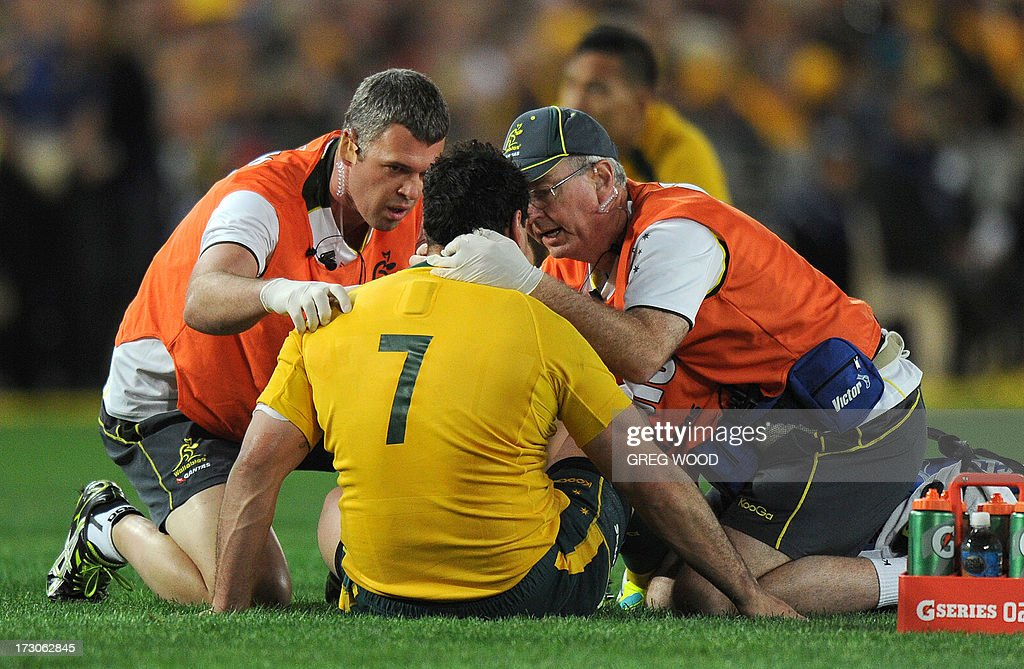 George Smith of Australia (C) is checked by trainers after a heavy clash against the British and Irish Lions during the third and final rugby union Test in Sydney on July 6, 2013. IMAGE STRICTLY RESTRICTED TO EDITORIAL USE - STRICTLY NO COMMERCIAL USE AFP PHOTO / Greg WOOD