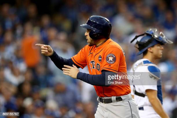 George Springer of the Houston Astros celebrates after scoring off of a single hit by Alex Bregman of the Houston Astros in the first inning and...