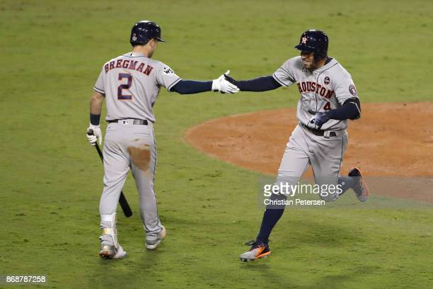 George Springer of the Houston Astros celebrates with Alex Bregman after hitting a solo home run during the third inning against the Los Angeles...
