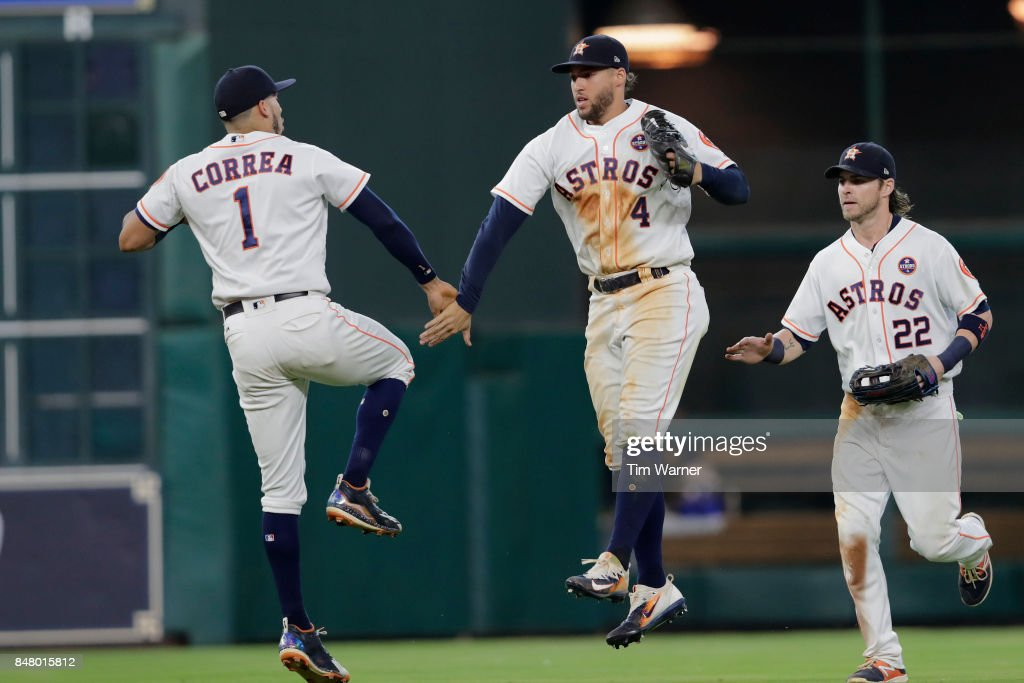 George Springer #4 of the Houston Astros celebrates with Carlos Correa #1 and Josh Reddick #22 after the game against the Seattle Mariners at Minute Maid Park on September 16, 2017 in Houston, Texas.
