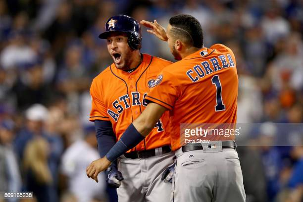 George Springer of the Houston Astros celebrates with Carlos Correa after hitting a tworun home run during the second inning against the Los Angeles...