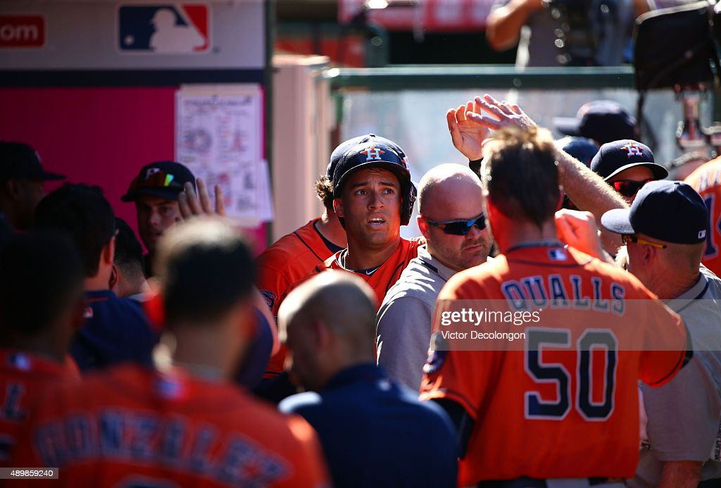 George Springer #4 of the Houston Astros celebrates with teammates in the dugout after scoring in the ninth inning against the Los Angeles Angels of Anaheim during the MLB game at Angel Stadium of Anaheim on September 13, 2015 in Anaheim, California. The Astros defeated the Angels 5-3.