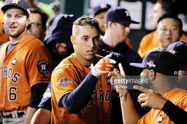 George Springer of the Houston Astros celebrates with teammates in the dugout after hitting a solo home run in the fifth inning against the Kansas...