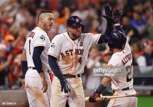 George Springer of the Houston Astros celebratres with Carlos Correa and Jose Altuve after hitting a solo home run during the seventh inning against...