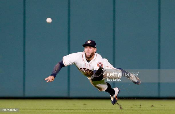 George Springer of the Houston Astros comes up short on a diving attempt on a line drive by Michael Taylor of the Washington Nationals in the fifth...