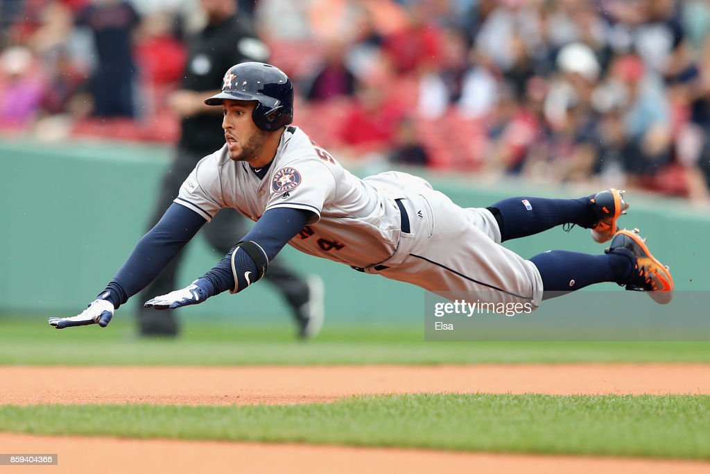 George Springer #4 of the Houston Astros dives towards second base after hitting a double in the first inning against the Boston Red Sox during game four of the American League Division Series at Fenway Park on October 9, 2017 in Boston, Massachusetts.