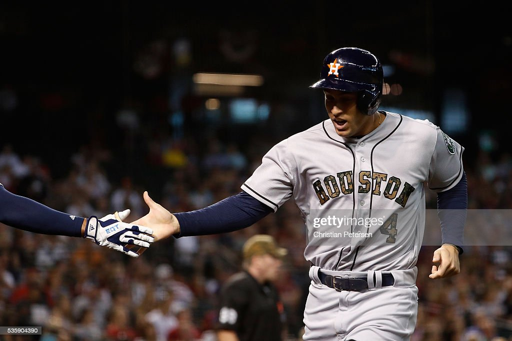 <a gi-track='captionPersonalityLinkClicked' href=/galleries/search?phrase=George+Springer&family=editorial&specificpeople=8060257 ng-click='$event.stopPropagation()'>George Springer</a> #4 of the Houston Astros high-fives a teammate after scoring a run against the Arizona Diamondbacks during the second inning of the MLB game at Chase Field on May 30, 2016 in Phoenix, Arizona.