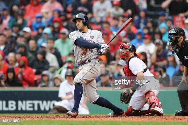 George Springer of the Houston Astros hits an RBI single in the second inning against the Boston Red Sox during game four of the American League...
