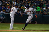 George Springer of the Houston Astros is congratulated by third base coach Gary Pettis after hitting a home run against the Oakland Athletics during...