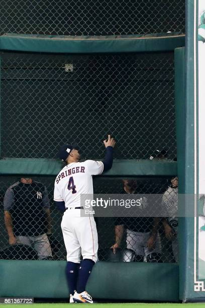 George Springer of the Houston Astros looks up at the ball stuck in the fence after Todd Frazier of the New York Yankees hit a groundrule double...