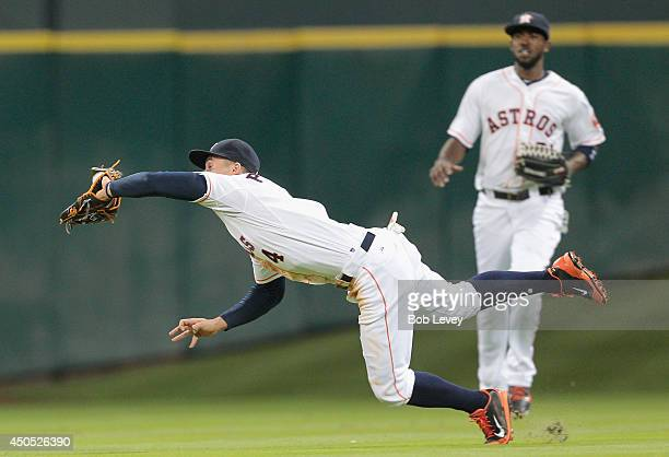 George Springer of the Houston Astros makes a diving catch in the fifth inning against the Arizona Diamondbacks at Minute Maid Park on June 12 2014...