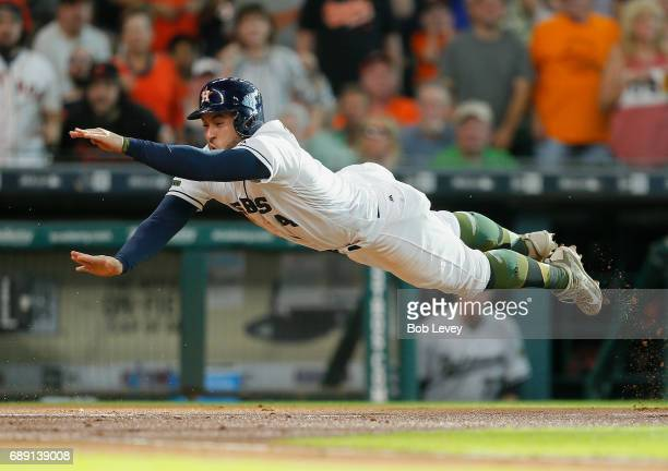 George Springer of the Houston Astros scores in the first inning as he dives past he tag of Caleb Joseph of the Baltimore Orioles in the first inning...