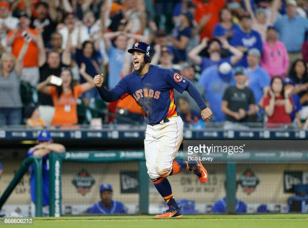 George Springer of the Houston Astros scores the winning run in the twelfth inning on an Evan Gattis walk by Matt Strahm of the Kansas City Royals at...