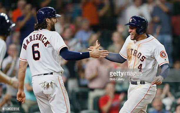 George Springer of the Houston Astros slaps the hand of Jake Marisnick after scoring in thr sixth inning Seattle Mariners at Minute Maid Park on...