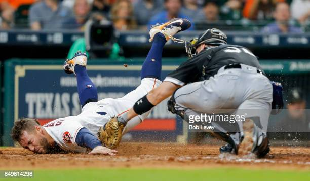George Springer of the Houston Astros slides around the tag of Kevan Smith of the Chicago White Sox to score in the eighth inning at Minute Maid Park...