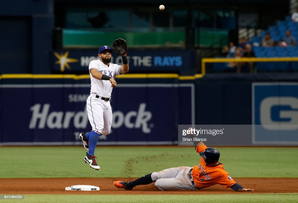 George Springer #4 of the Houston Astros slides into second base ahead of second baseman Rougned Odor #12 of the Texas Rangers before being called out on batter interference by Alex Bregman while attempting to steal second base during the first inning of a game on August 31, 2017 at Tropicana Field in St. Petersburg, Florida.