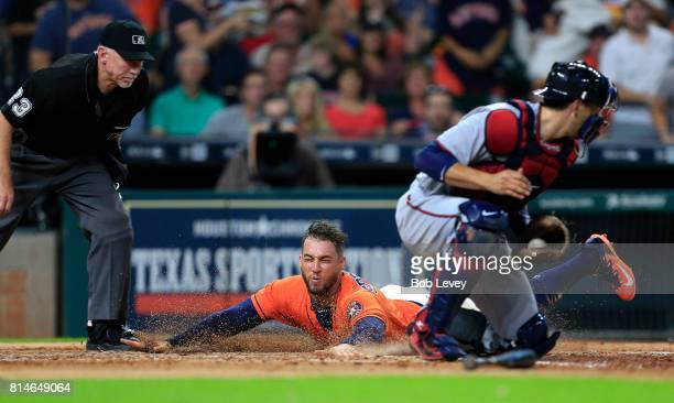 George Springer of the Houston Astros slides safely behind Jason Castro of the Minnesota Twins in the third inning at Minute Maid Park on July 14...