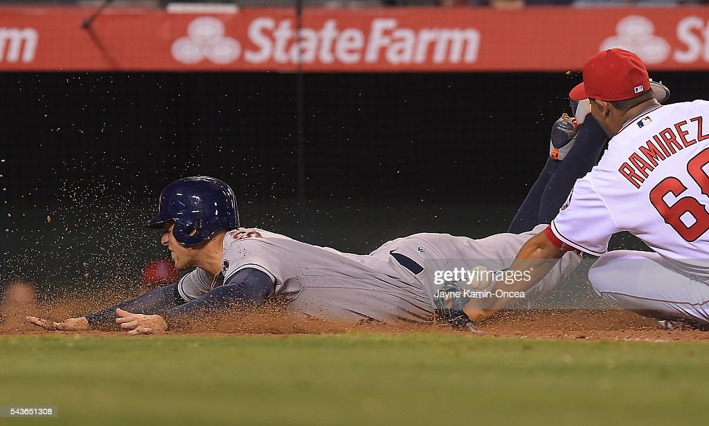 <a gi-track='captionPersonalityLinkClicked' href=/galleries/search?phrase=George+Springer&family=editorial&specificpeople=8060257 ng-click='$event.stopPropagation()'>George Springer</a> #4 of the Houston Astros slides under the tag attempt by JC Ramirez #66 of the Los Angeles Angels as he scored on a wild pitch in the ninth inning of the game at Angel Stadium of Anaheim on June 27, 2016 in Anaheim, California. The Houston Astros won 4-2.